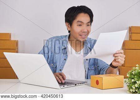 Smile Online Merchant Or Casual Businessman In Online Store Check Product Detail In Paper Sheet
