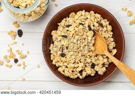 Healthy Breakfast. Muesli With Dried Grapes In A Clay Bowl On A White Wooden Table. Muesli Is Scatte