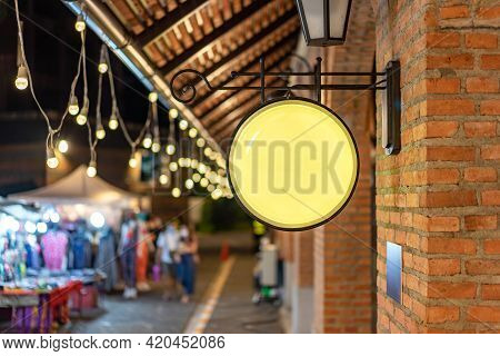 The Circle Yellow Lightbox Has Hung On The Wall In Front Of The Brick Pole In A Tungsten Ambient Env