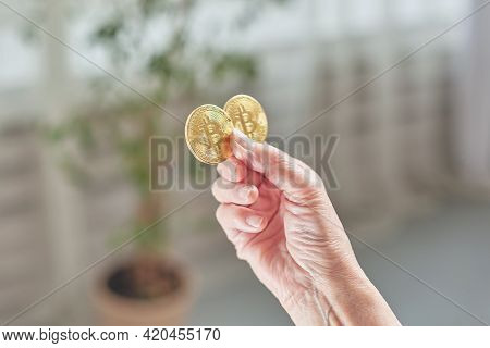 Old Woman Holds Bitcoin Coins In Her Hand. Senior Citizen Happy Life Concept