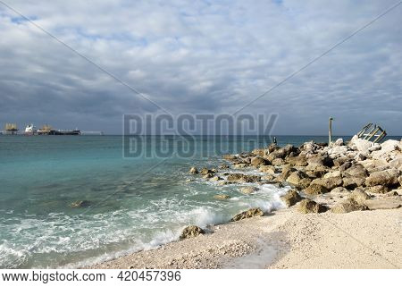 The View Of Grand Bahama Island Beach Near House Ruins And A Cargo Ship In A Background Moored In A