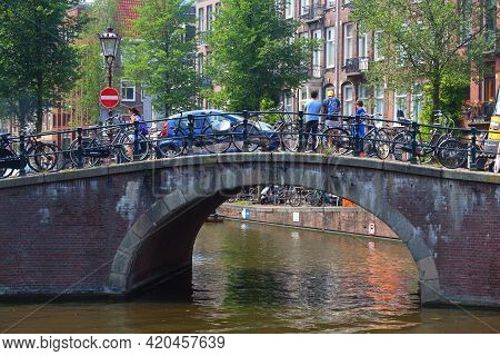 Amsterdam, Netherlands - July 7, 2017: People Cross A Canal Bridge In Amsterdam, Netherlands. Amster