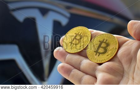 Calgary, Alberta, Canada. May 14, 2021. A Person Holding A Couple Bitcoin With The Tesla Car On The