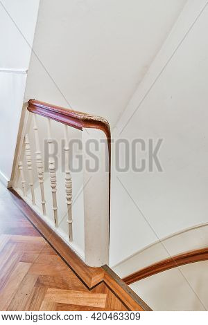 Element Of Stairway With White Decorative Balusters And Wooden Railings In Vintage Style Apartment