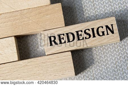 Redesign - Word On A Wooden Bar On A Gray Background. Business Concept