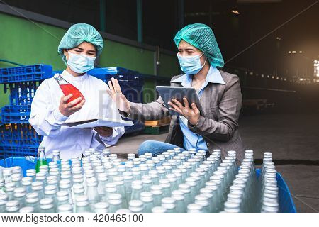 An Asian Attractive Woman Factory Manager And Staff Wearing A Masks, Is Counting Stock And Check Pro