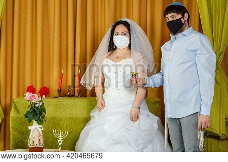 During The Chuppah Ceremony In The Synagogue, The Bride And Groom Stand Next To The Groom Holding A