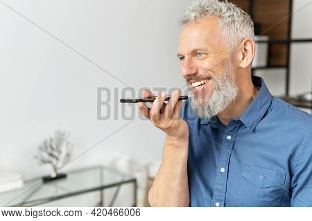 Senior Cheerful Man Sending Voice Message, Using Smartphone App For Recording And Recognizing Voice