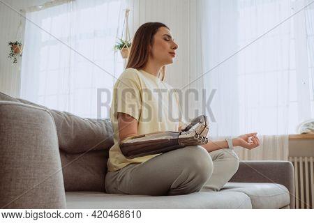 Blonde Woman With Stylish Prosthesis Arm Meditates On Sofa