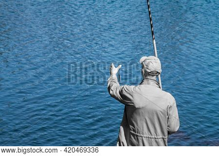 Gray Fisherman On The Background Of Blue Water Of The Lake. The Fisherman Caught A Small Fish. The F