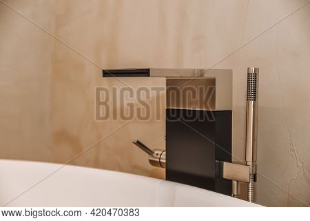 Expensive Chrome Faucet With Wide Spout And Minimalist Design Of Shower Nozzle In Bathroom