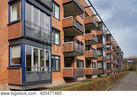 Apartment Building Of Red Bricks With Several Floors And Corbels And Balcony