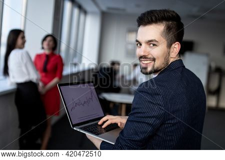 Young Smiling Businessman, The Laptop In The Hands Of A Businessman.