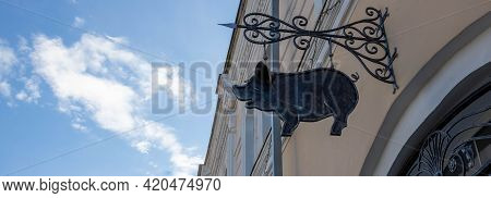Forged Metal Pig Hanging On The Wall Of A House On The Street.