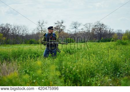 Airsoft Player In Camouflage Military Uniform Holds A Rifle In His Hands In The Field