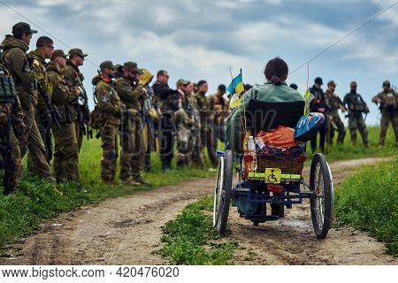A Young Disabled Man In A Wheelchair Against The Background Of A Group Of Soldiers In Military Unifo
