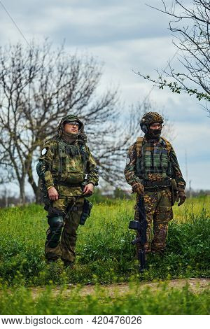 Two Airsoft Players In Outfit With Weapons In The Field