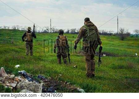 Airsoft Players With Weapons In Their Hands Are Walking Across The Field