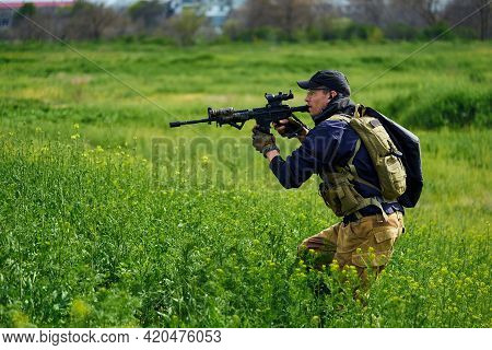 Airsoft Player In Military Uniform Aims At The Enemy