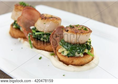 Seared Scallops Sitting Atop A Bed Of Spinach Served As A Threesome For Your Seafood Appetite.