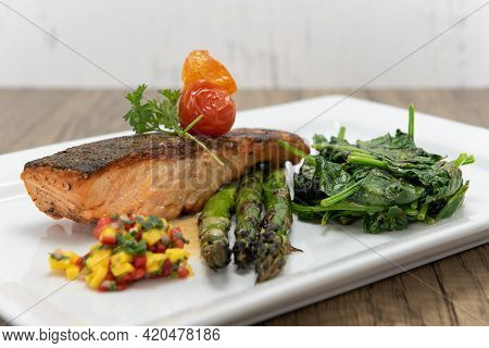 Grilled Salmon Steak Served With Asparagus And Spinach To Indulge That Seafood Appetite.