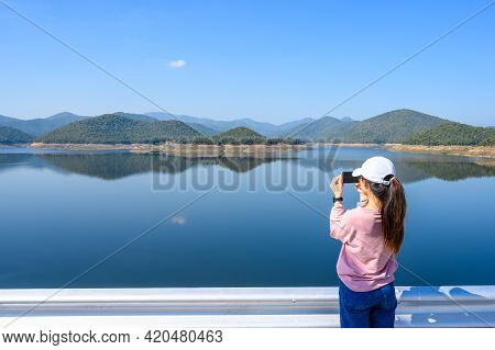 Back View Of Young Tourist Woman Taking A Picturesque Of The Nature In Mae Kuang Dam, Chiang Mai Pro