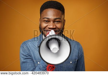 Young African American Guy Making Annoucement With Megaphone Against Yellow Background