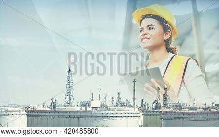 Double Exposure Of Smiling Engineer Wearing Helmet Safety And Holding Tablet With Blurred Oil Refine