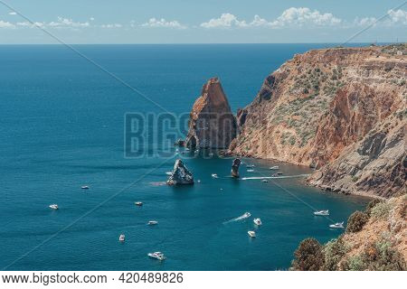 Boats And Yachts In The Rocky Bay With Crystal Clear Azure Sea On A Sunny Day. Calm Sea On A Backgro