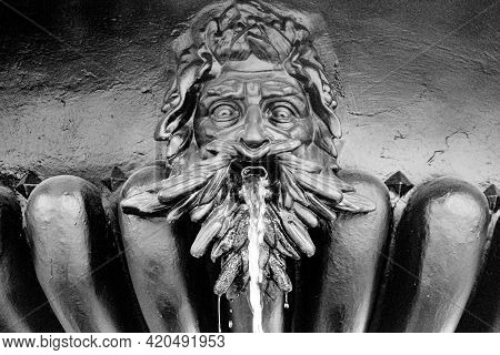 Fountain With A Statue Of A Mans Head, Water Flows From His Mouth