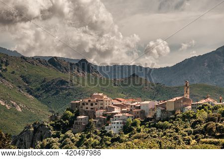 Clouds Hang Over The Mountains Behind The Village Of Montemaggiore In The Balagne Region Of Corsica