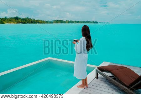 Luxury hotel vacation woman drinking breakfast coffee relaxing at ocean view from overwater villa suite terrace wearing bathrobe in the morning. Resort travel lifestyle guest enjoying room service.