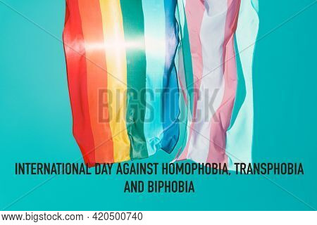 the text international day against homophobia, transphobia and biphobia, and a gay pride flag and a transgender pride flag waving on the blue sky, moved by the wind, with a sunbeam
