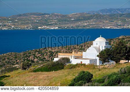 Scenic view of Milos island, Aegean sea and Greek Orthodox traditional whitewashed church. Milos island, Greece
