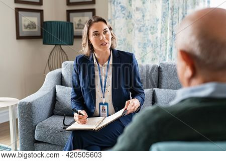 Mature social worker talking to senior man and taking notes of health progress. Mid adult woman in formal clothing visiting old man at home for medical history. Support worker talking to elder.