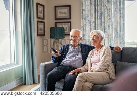 Happy senior couple using remote control to change channel. Seniors watch TV for entertainment while man using remote control. Wife and old man sitting on couch in living room with television show.