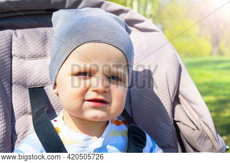 Adorable Happy Caucasian Baby Boy Sitting In Grey Stroller In Park. Summer Day. Child Is Strapped In
