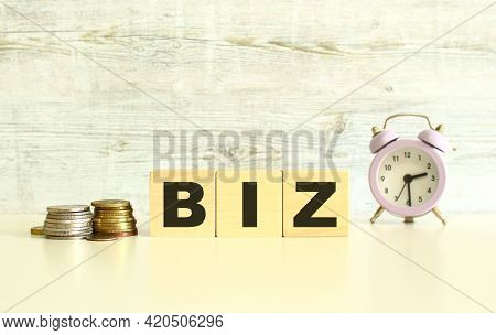 There Are Three Wooden Cubes With Letters On The Table Next To The Coins. The Word Biz. On A Gray Ba
