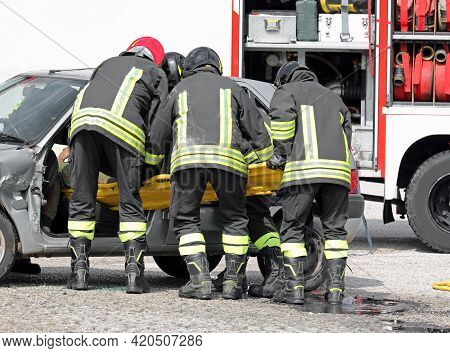 Firefighters At The Rescue To The Injured With A Stretcher After The Car Accident