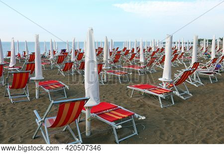 Umbrellas And Deck Chairs Without People On The Beach Waiting For Tourists In The Summer Season That