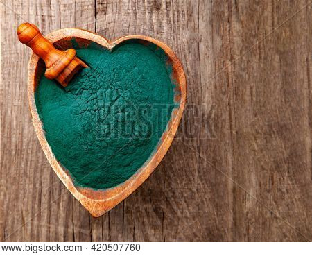 Ground Spirulina in bowl on wood background, top view on heart shape dish with superfood