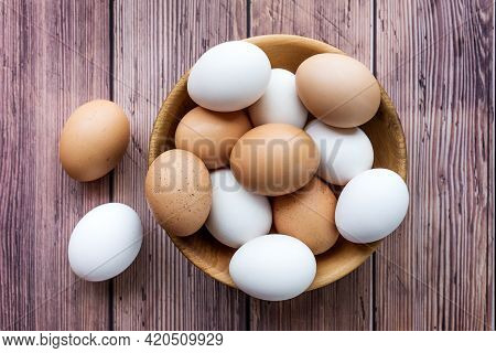 Wooden Bowl With Brown And White Chicken Eggs On Wood Table. Brown And White Eggs In Bowl On Wood Ba