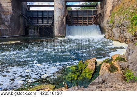 Flowing Water With Water Spray From The Open Sluice Gates Of A Small Dam