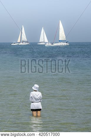 A Young Woman Dressed In A White Top And Hat, Standing In Shallow Sea Water On A Sunny Day, Watching