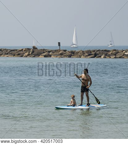 Tel Aviv, Israel - April 15th, 2021:a Man And A Boy On A Surfboard Off The Shore Of Tel Aviv, On A S