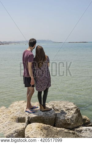 A Young Couple Standing On Some Rocks At The Tel Aviv, Israel, Beach, On A Clear, Sunny Day..