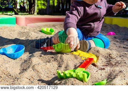 Unrecognizable Little Caucasian Boy Sitting In Sandbox With Toys On Sunny Summer Day In Big City. Ch