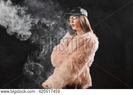 Sexy Trendy Rap Woman In Pink Fur Coat And Cap Smoke Electronic Cigarette. Pink Studio Background Sh