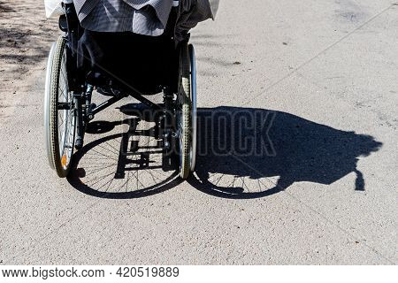 Shadow Of A Person In The Wheelchair And The Tires On Asphalt. Shadow Of A Woman With A Disability S