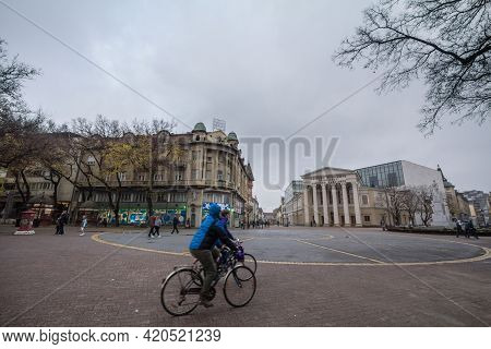 Subotica, Serbia - November 17, 2020: Speed Blur On Two People Biking In Front Of The Facade Of Nati